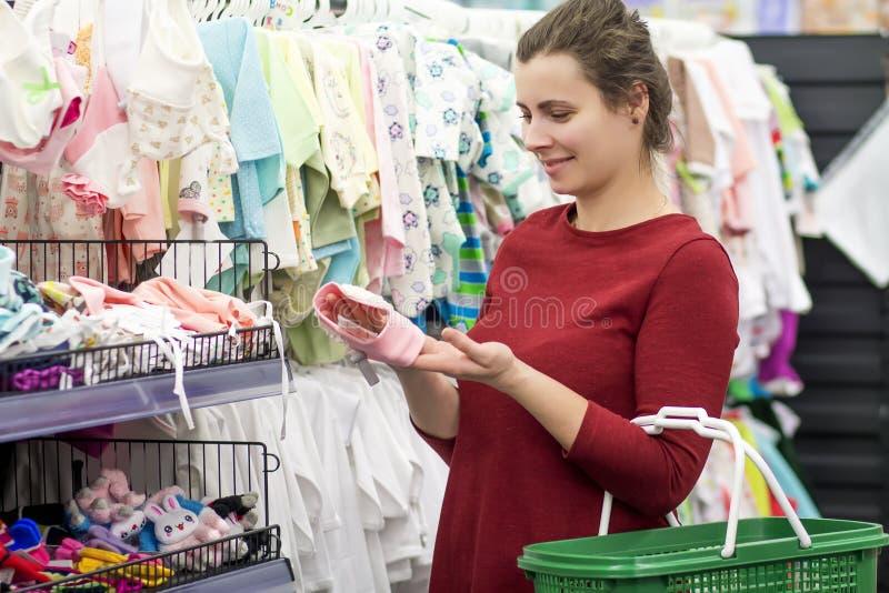 A mãe nova escolhe a roupa do ` s das crianças em uma loja de roupa foto de stock