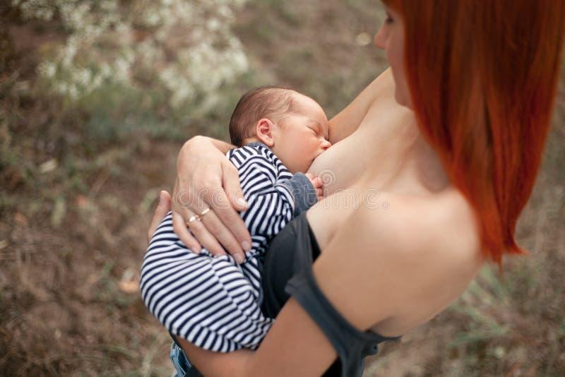 A mãe nova feliz amamenta o bebê recém-nascido na caminhada fotografia de stock royalty free