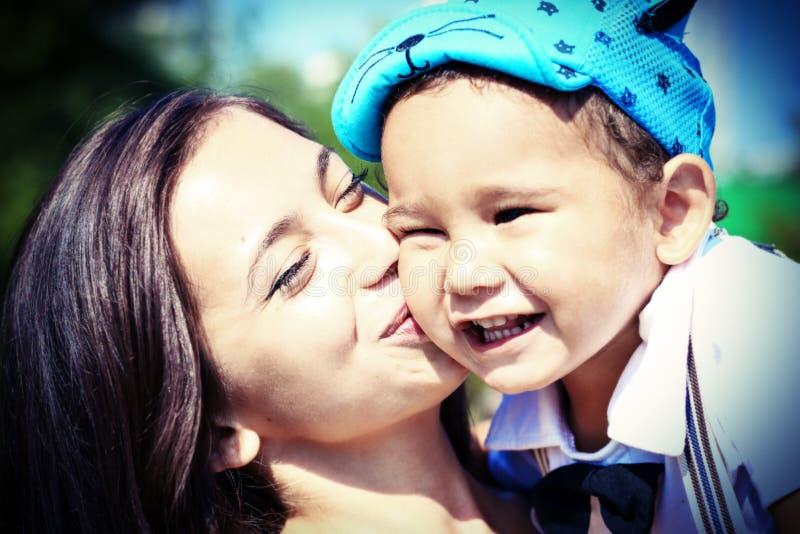A mãe nova feliz beija seu filho pequeno fotografia de stock
