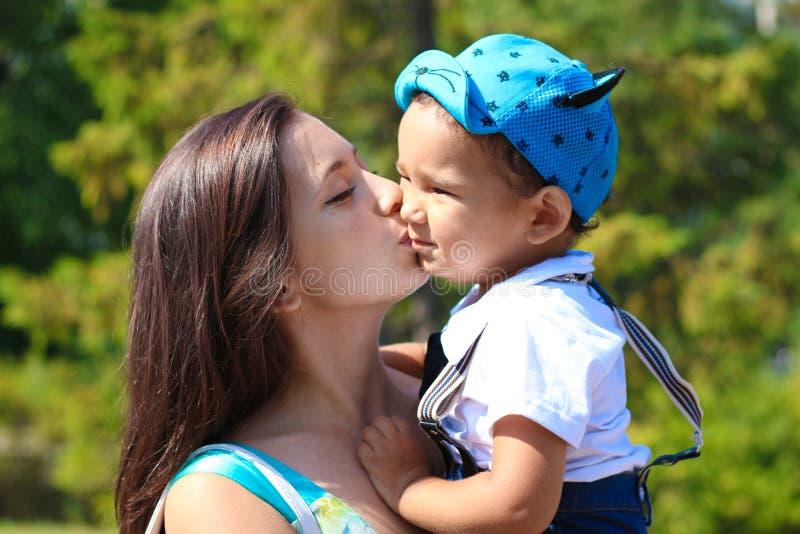 A mãe nova feliz beija seu filho pequeno imagem de stock