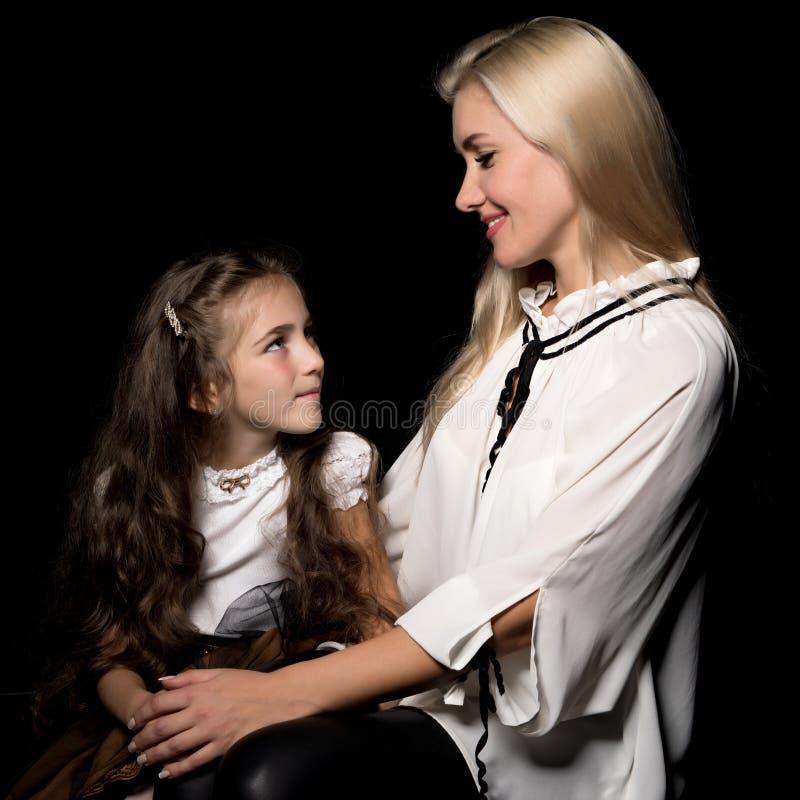 Mãe nova feliz com sua filha em suas mãos em um CCB preto fotografia de stock