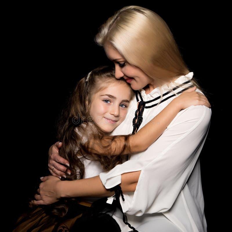 Mãe nova feliz com sua filha em suas mãos em um CCB preto foto de stock