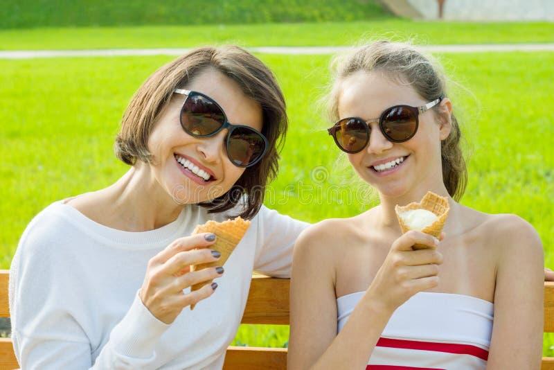 A mãe nova feliz e a filha bonito de um adolescente em uma cidade estacionam comer o gelado, a fala e o riso imagens de stock royalty free