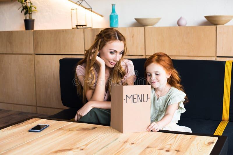 mãe nova feliz e menu adorável da leitura da filha do ruivo imagens de stock