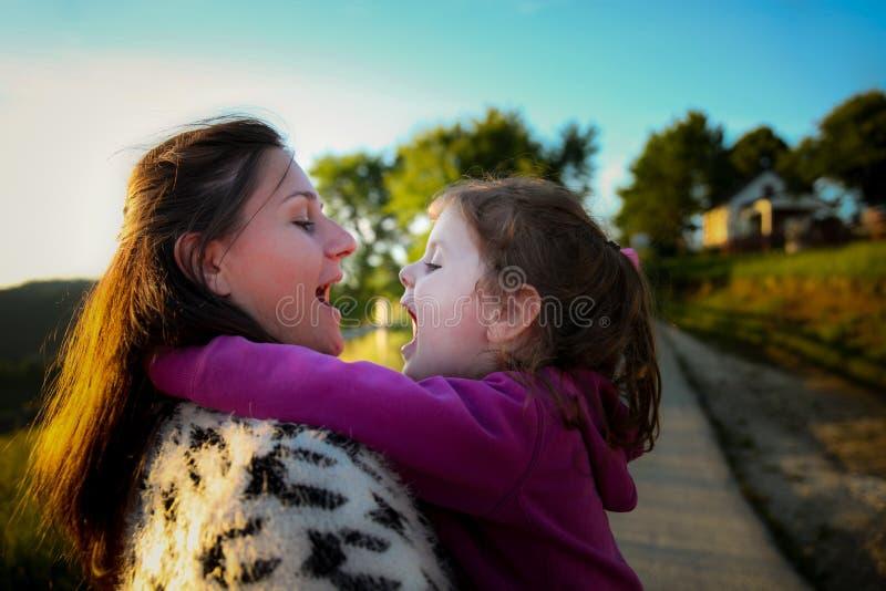 Mãe nova feliz que abraça sua filha doce no fundo de um prado bonito do país imagens de stock royalty free