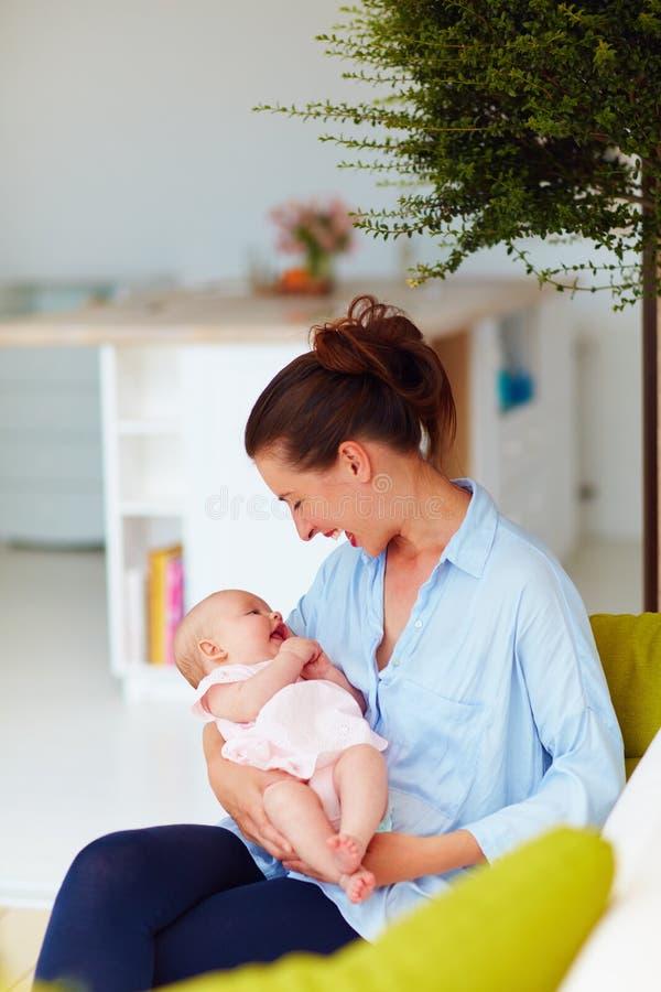 Mãe nova feliz que aprecia uma comunicação com a filha pequena foto de stock