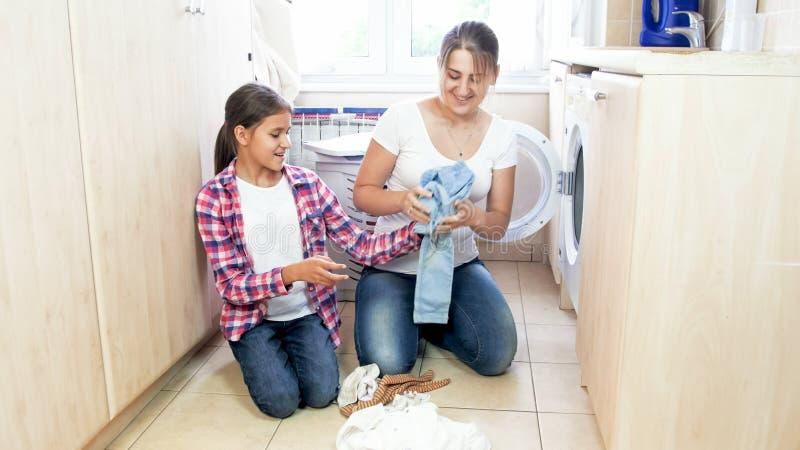 Mãe nova feliz que faz a lavanderia com sua filha do adolescente em casa imagens de stock