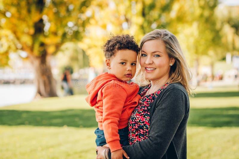 Mãe nova feliz que guarda o menino doce da criança fotografia de stock