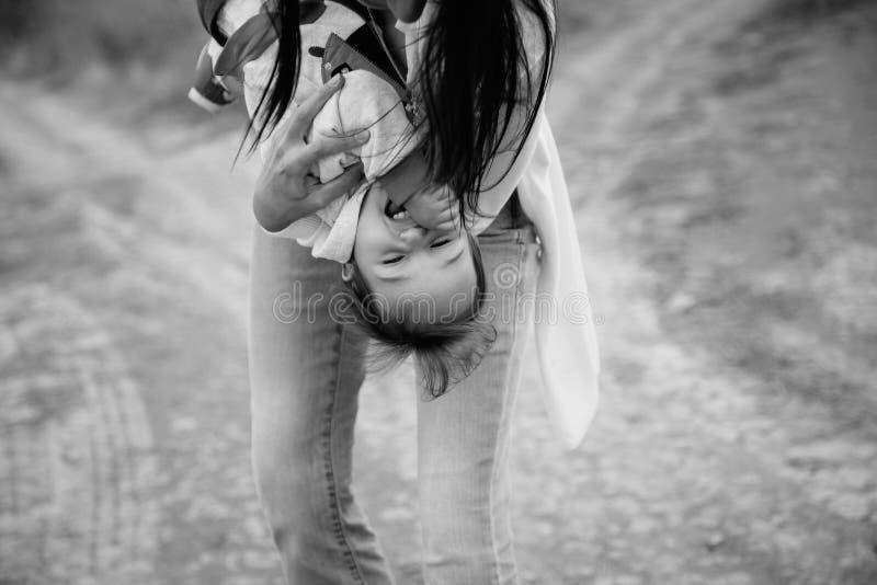 Mãe nova feliz que joga com uma filha pequena, mantendo a menina pequena de cabeça para baixo, fora fundo imagens de stock royalty free