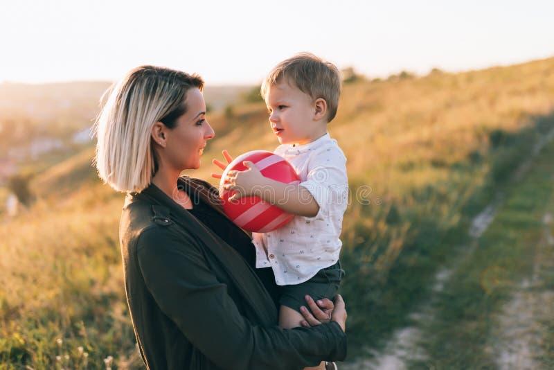 mãe nova feliz que leva o filho pequeno adorável com vermelho imagens de stock