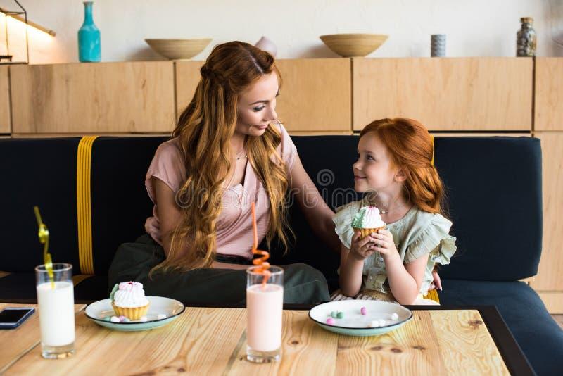 mãe nova feliz que olha a filha bonito do ruivo que come o queque imagens de stock royalty free