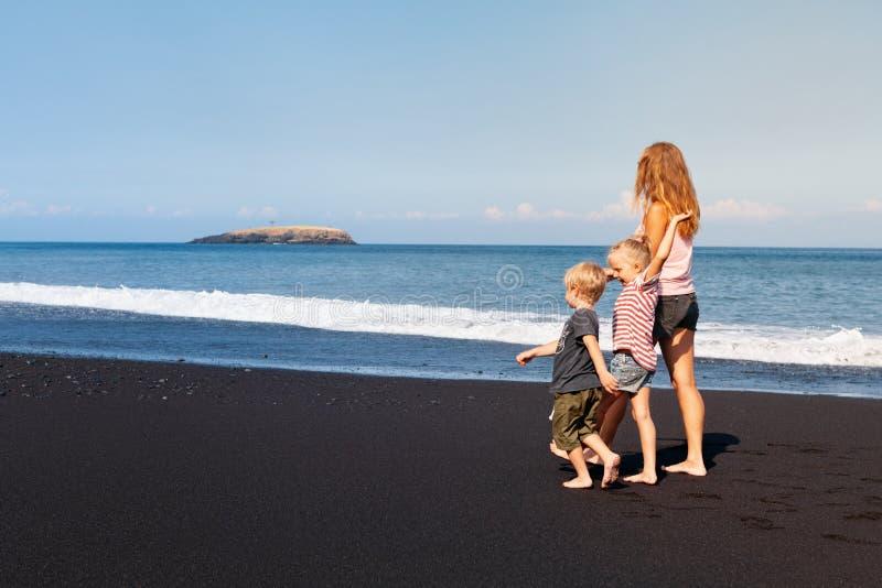 Mãe nova, filha, corrida do filho pela praia preta da areia foto de stock