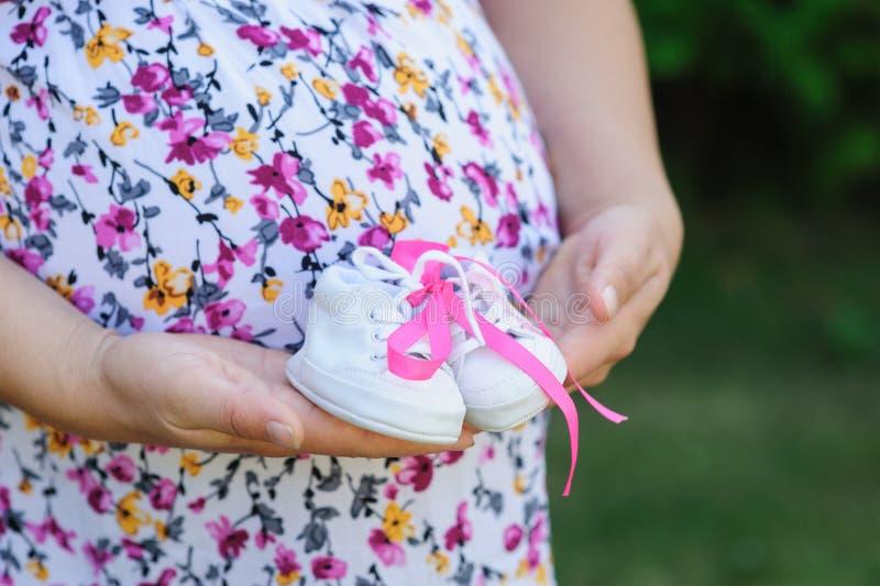 A mãe nova grávida guarda a criança das sapatas do branco foto de stock royalty free