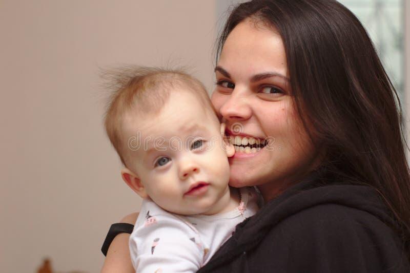 a mãe nova guarda seu bebê engraçado, doce em seus braços fotos de stock royalty free