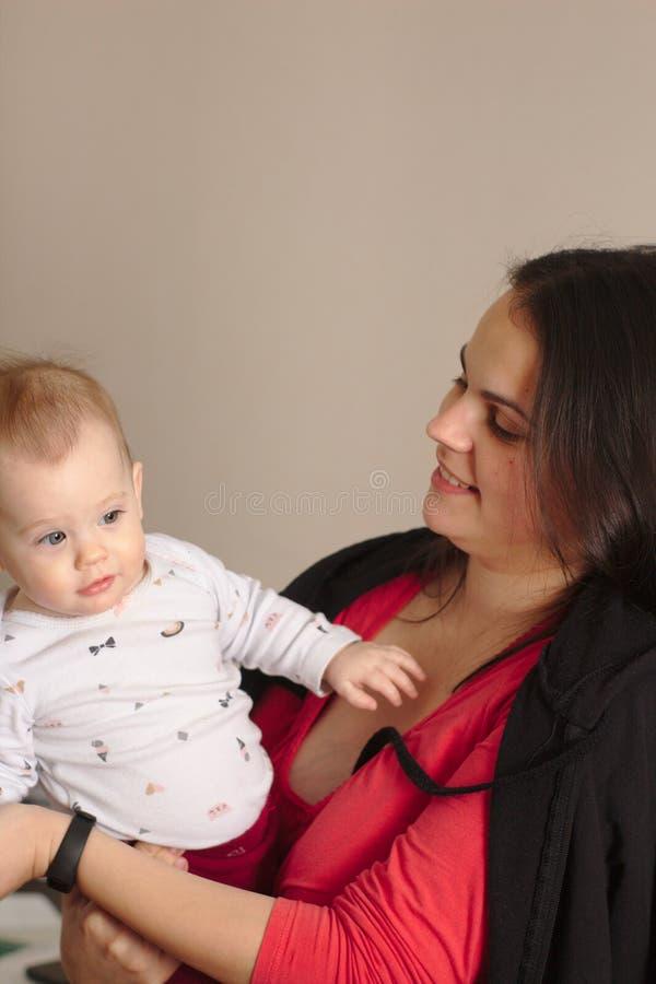 a mãe nova guarda seu bebê engraçado, doce em seus braços foto de stock royalty free