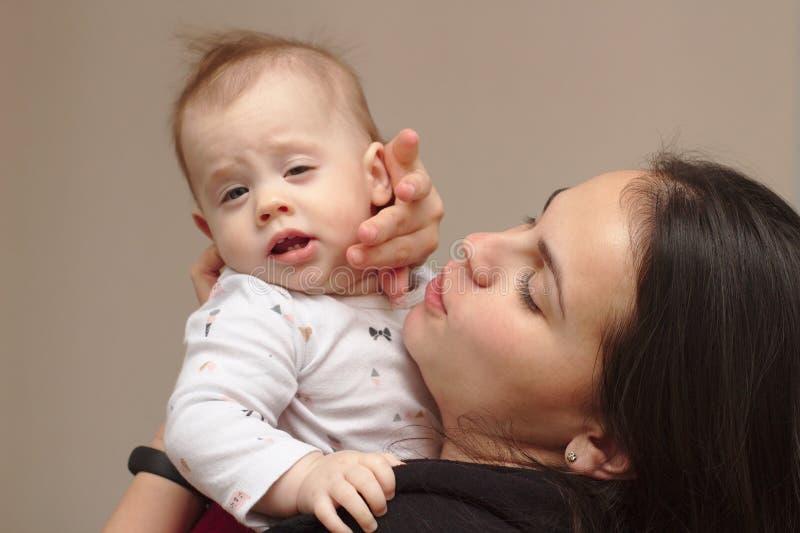 a mãe nova guarda seu bebê engraçado, doce em seus braços imagem de stock royalty free
