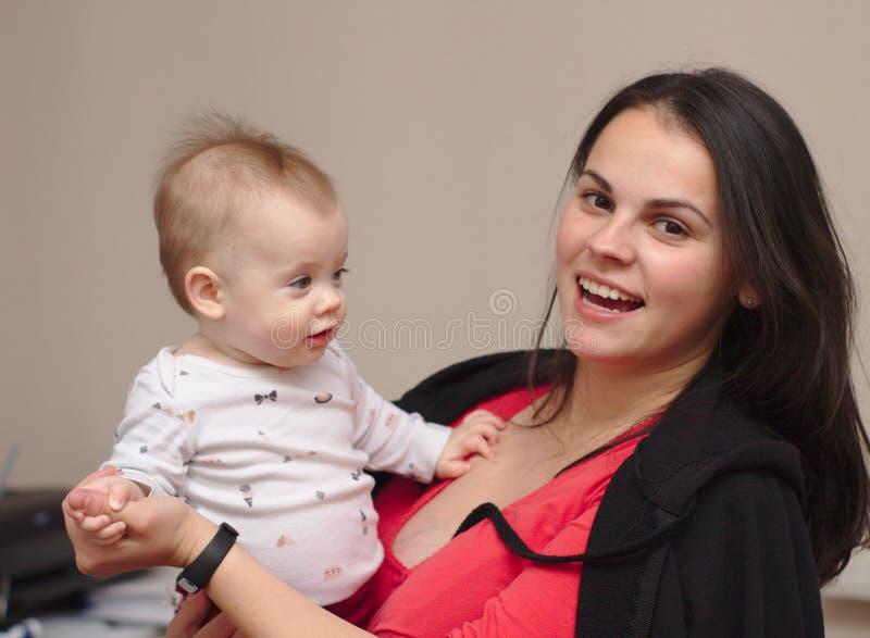 a mãe nova guarda seu bebê engraçado, doce em seus braços fotografia de stock royalty free