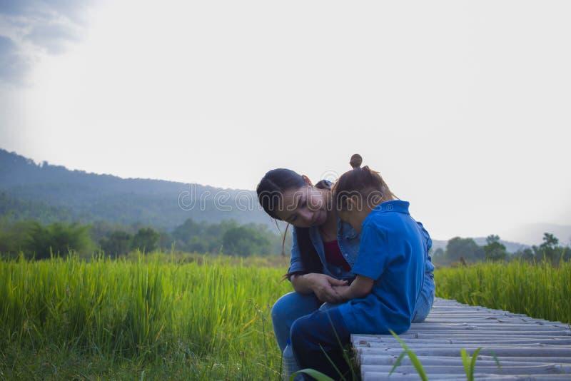 Mãe nova que abraça e que acalma um menino longo pequeno de grito do cabelo, uma mãe asiática tentando consolar para baixo e acal imagens de stock royalty free