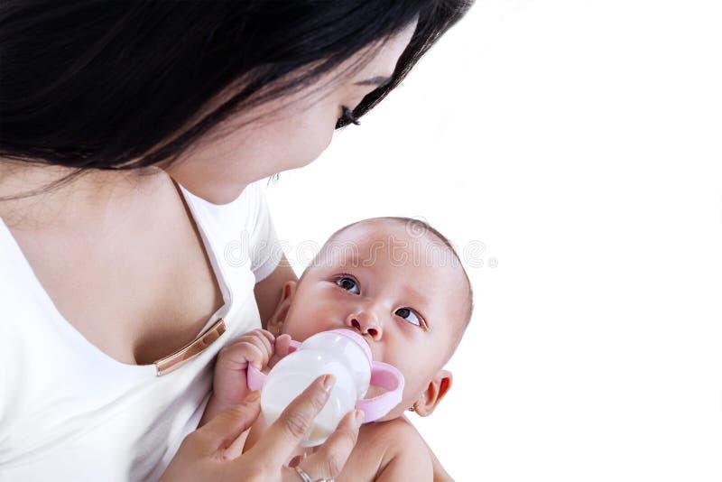 Mãe nova que alimenta seu bebê isolado imagens de stock