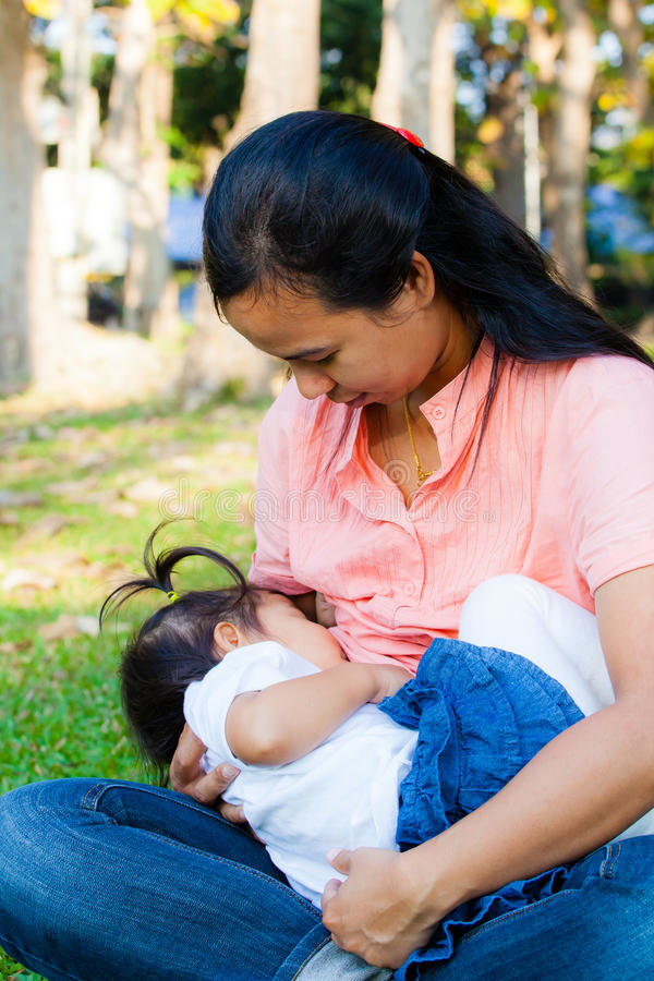 Mãe nova que alimenta seu bebê no parque imagem de stock
