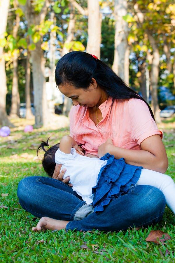 Mãe nova que alimenta seu bebê no parque foto de stock