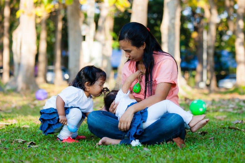 Mãe nova que alimenta seu bebê no parque imagem de stock royalty free