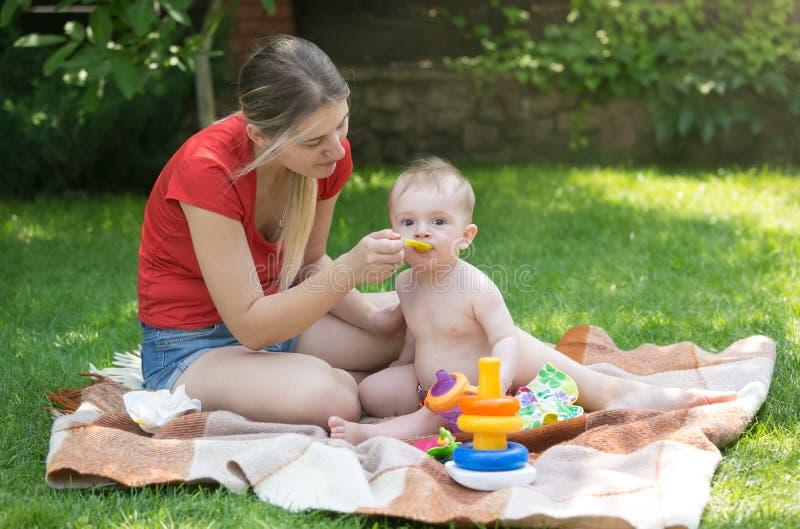 Mãe nova que alimenta seu bebê no piquenique no parque fotografia de stock