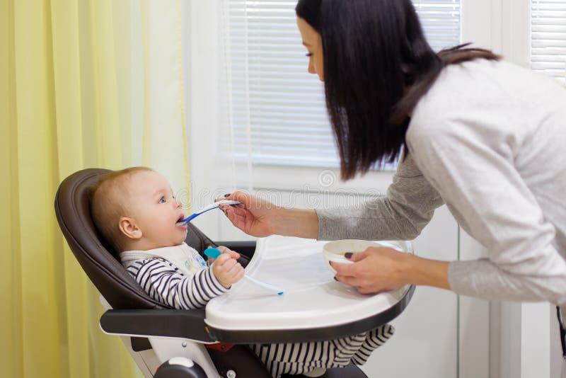 Mãe nova que alimenta seu filho pequeno do bebê com papa de aveia, que se sentando na cadeira alta do bebê para alimentar imagem de stock