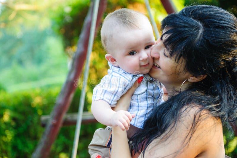 Mãe nova que beija seu filho pequeno imagem de stock royalty free