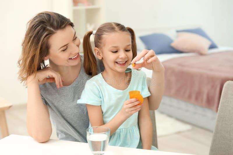 Mãe nova que dá o comprimido a sua filha em casa imagens de stock royalty free