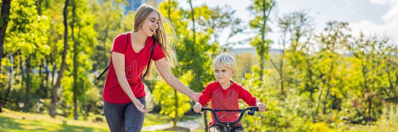 Mãe nova que ensina a seu filho como montar uma bicicleta na BANDEIRA do parque, FORMATO LONGO foto de stock royalty free