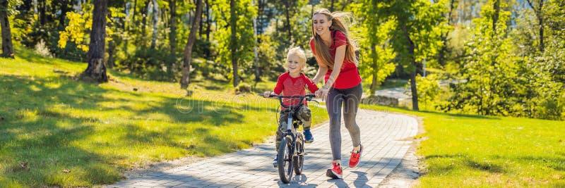 Mãe nova que ensina a seu filho como montar uma bicicleta na BANDEIRA do parque, FORMATO LONGO fotografia de stock royalty free