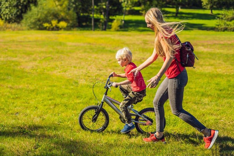 Mãe nova que ensina a seu filho como montar uma bicicleta no parque imagens de stock