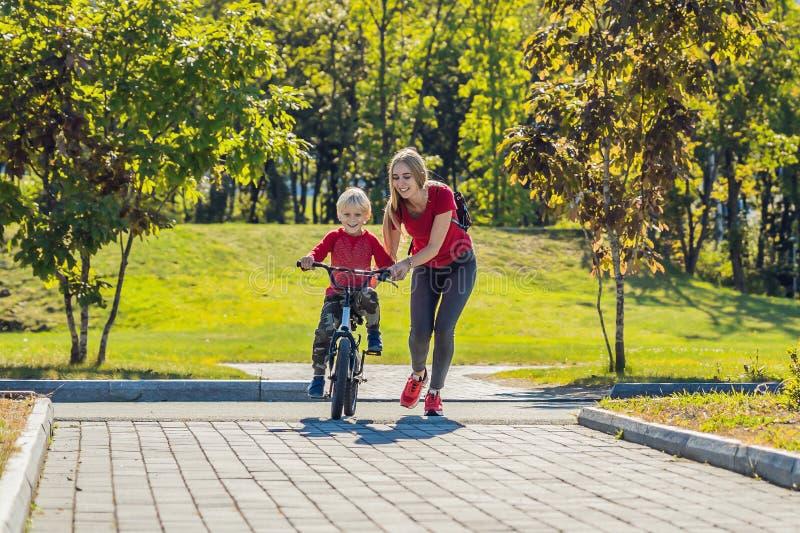 Mãe nova que ensina a seu filho como montar uma bicicleta no parque fotografia de stock royalty free