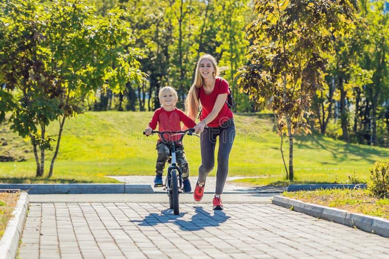 Mãe nova que ensina a seu filho como montar uma bicicleta no parque fotos de stock royalty free