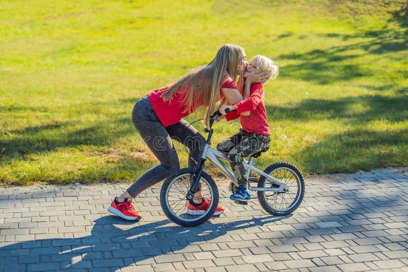 Mãe nova que ensina a seu filho como montar uma bicicleta no parque foto de stock royalty free