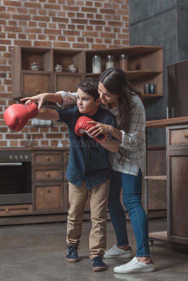 Mãe nova que ensina seu filho pequeno nas luvas de encaixotamento corretas foto de stock