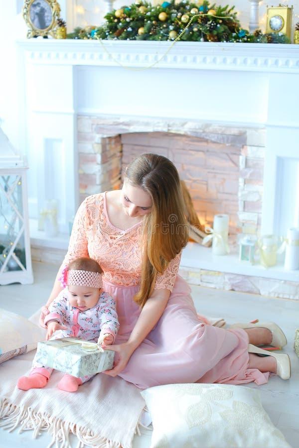 A mãe nova que gifting o presente pequeno da filha próximo decorou a chaminé fotos de stock royalty free