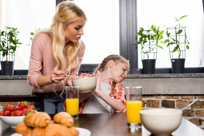 mãe nova que guarda a bacia com flocos de milho e que alimenta a filha pequena foto de stock royalty free