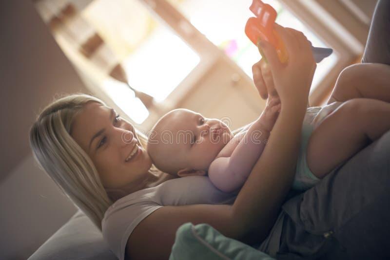 Mãe nova que guarda o brinquedo e que joga com seu bebê pequeno fotos de stock