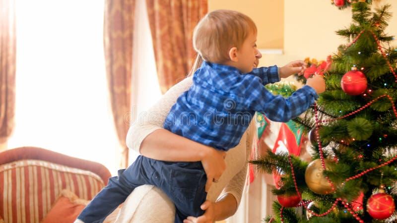 Mãe nova que guarda o filho pequeno e que ajuda o a decorar a árvore de Natal fotografia de stock royalty free