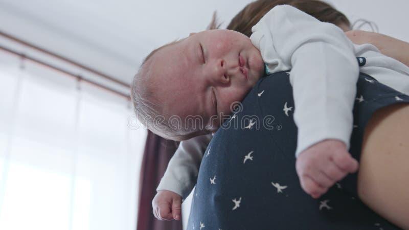 Mãe nova que guarda seu bebê em seu ombro fotografia de stock royalty free