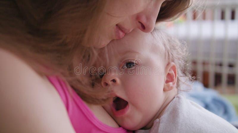 Mãe nova que guarda seu bebê em seus braços imagem de stock