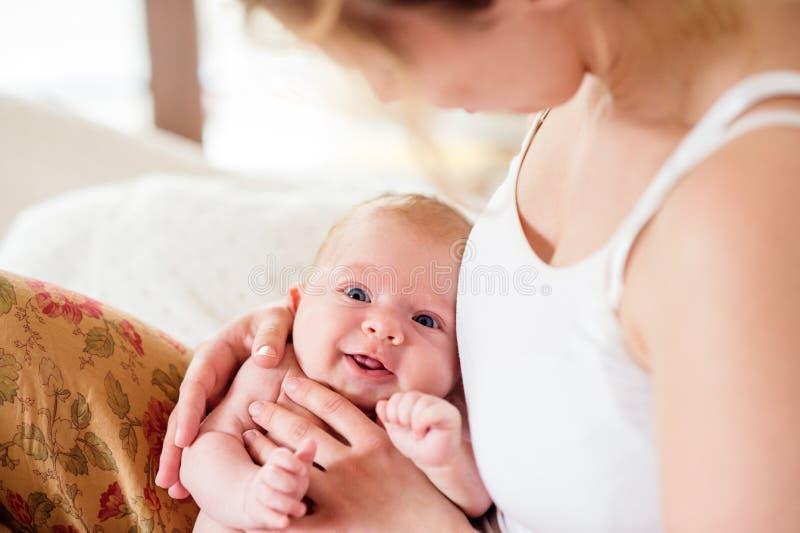 Mãe nova que guarda seu filho recém-nascido do bebê, quarto home imagem de stock royalty free