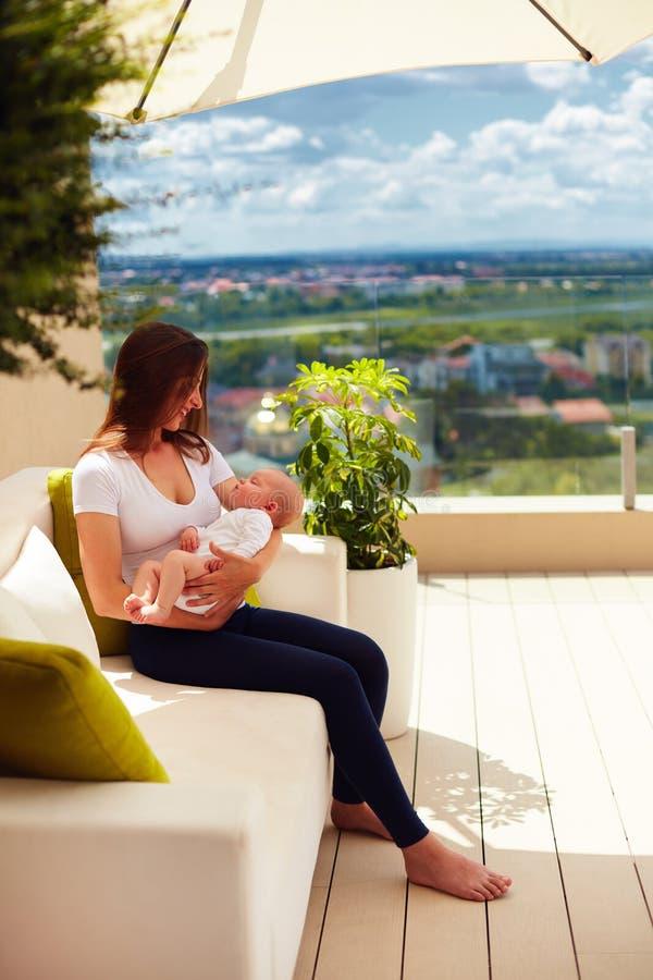 A mãe nova que guarda sobre entrega o bebê infantil, ao sentar-se no terraço do pátio do verão imagens de stock royalty free