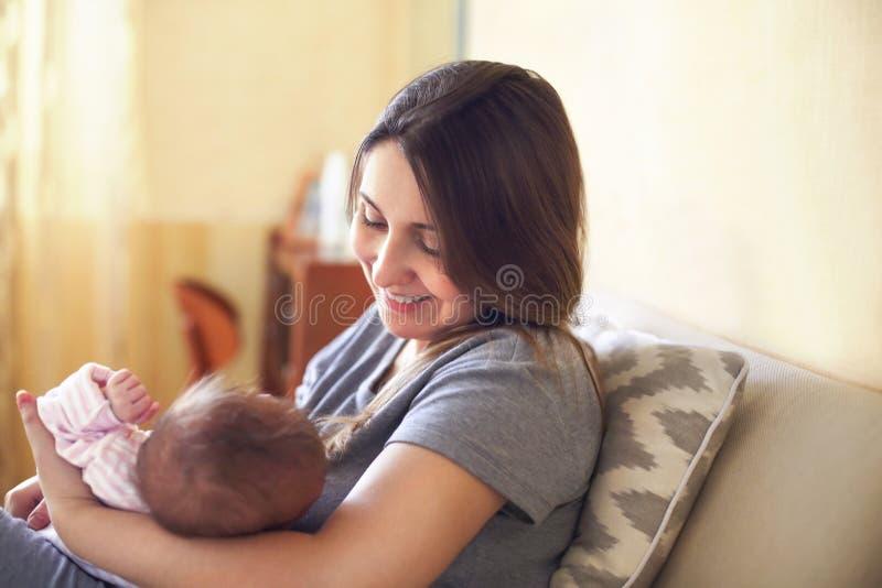 Mãe nova que guarda sua criança recém-nascida Bebê dos cuidados da mamã fotos de stock royalty free