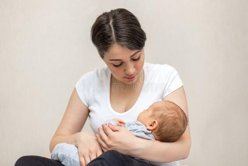 Mãe nova que guarda sua criança recém-nascida Bebê dos cuidados da mamã fotografia de stock royalty free