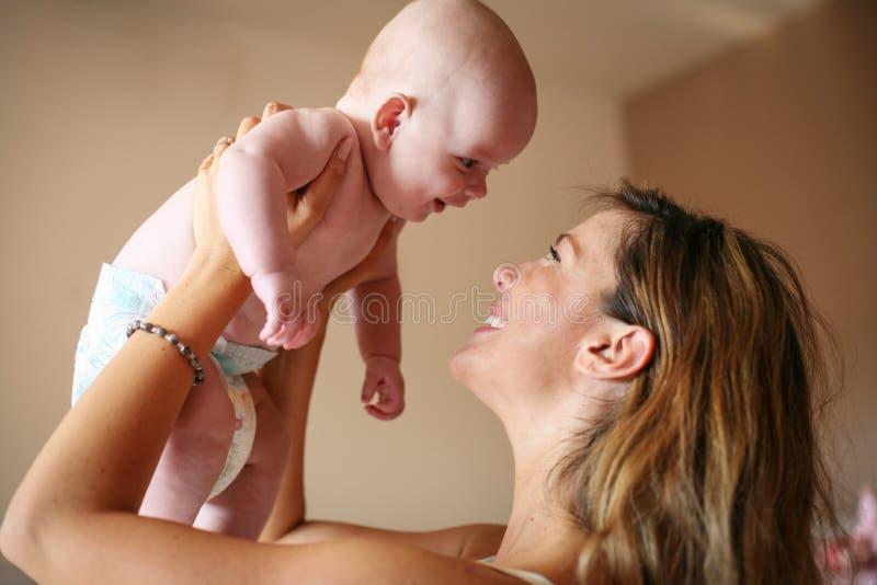 Mãe nova que joga com seu bebê imagens de stock royalty free