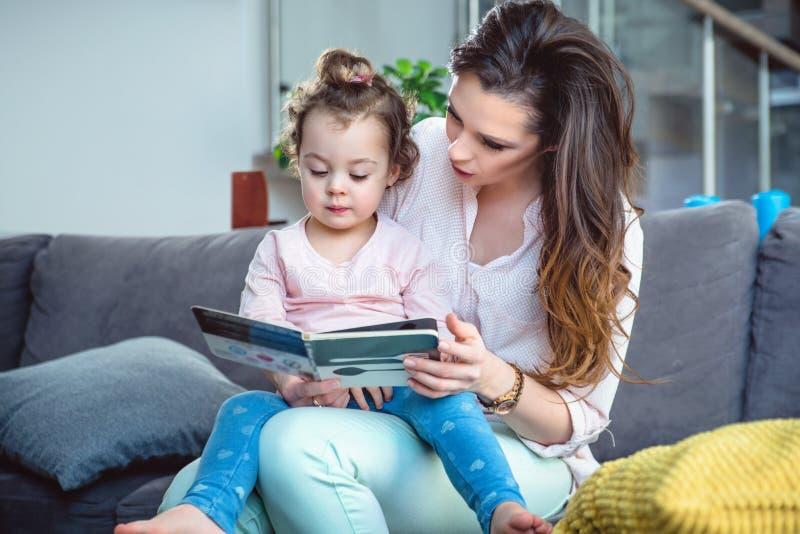 Mãe nova que lê um livro com seu bebê pequeno fotos de stock