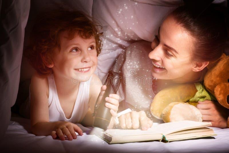 Mãe nova que lê um livro a sua criança bonita fotos de stock